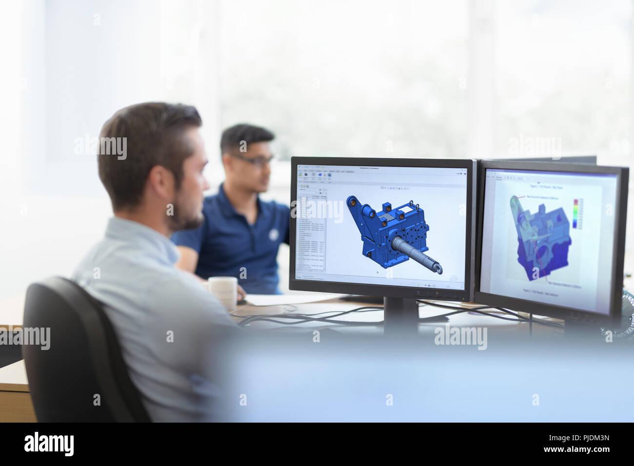 Los ingenieros que diseñaron las cajas utilizando el diseño asistido por ordenador (CAD) en la caja de software factory Imagen De Stock