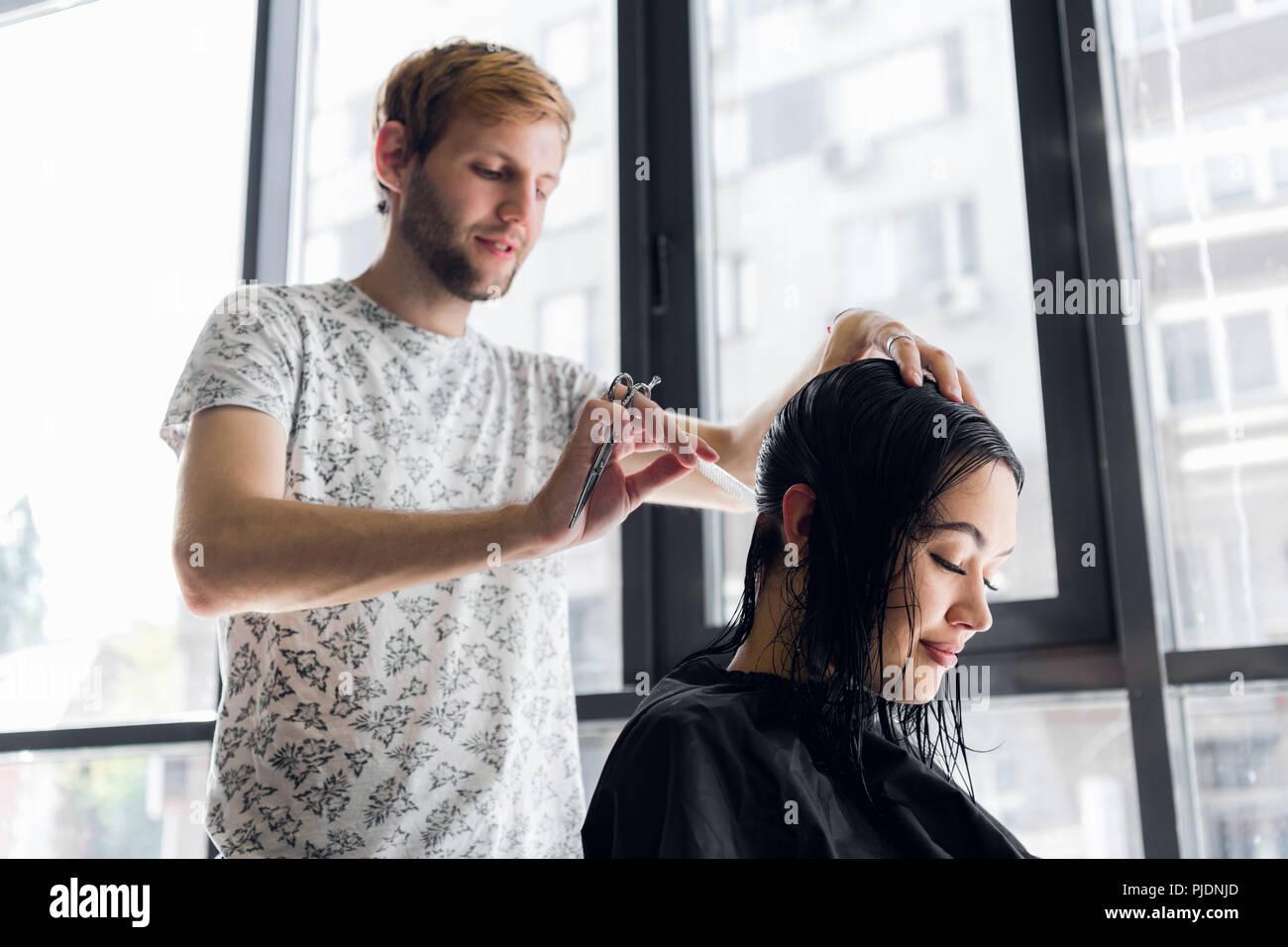 Peluquería el corte de cabello del cliente con tijeras de peluquería en primer plano. Usando un peine Imagen De Stock