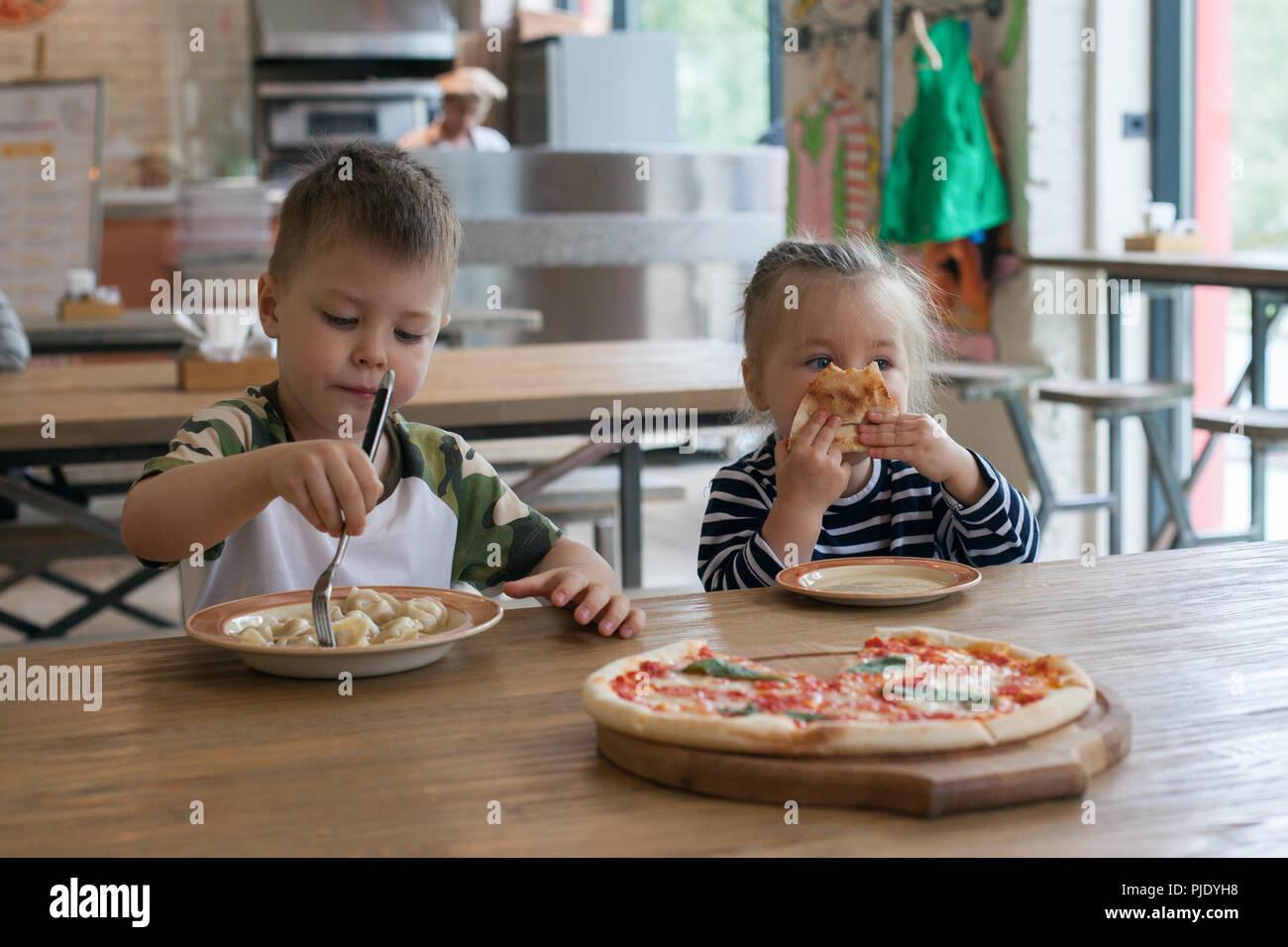 Los niños comen pizza y dumplings de carne en el café. Los niños que comen alimentos poco sanos en interiores. Los hermanos en la cafetería, el concepto de vacaciones de la familia. Imagen De Stock