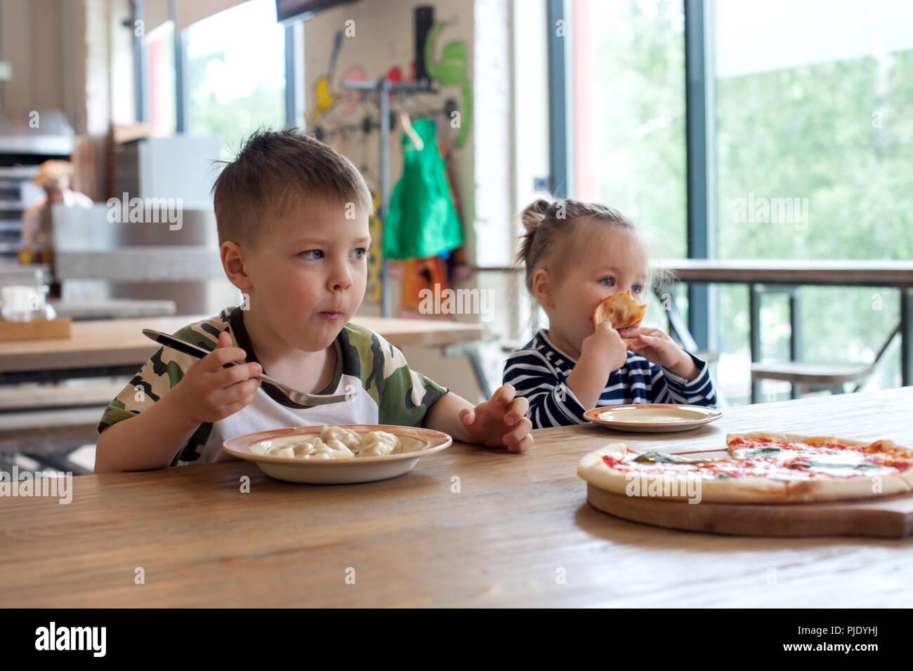 Los niños comen pizza y dumplings de carne en el café. Los niños que comen alimentos poco sanos en interiores. Los hermanos en la cafetería, el concepto de vacaciones de la familia. Foto de stock