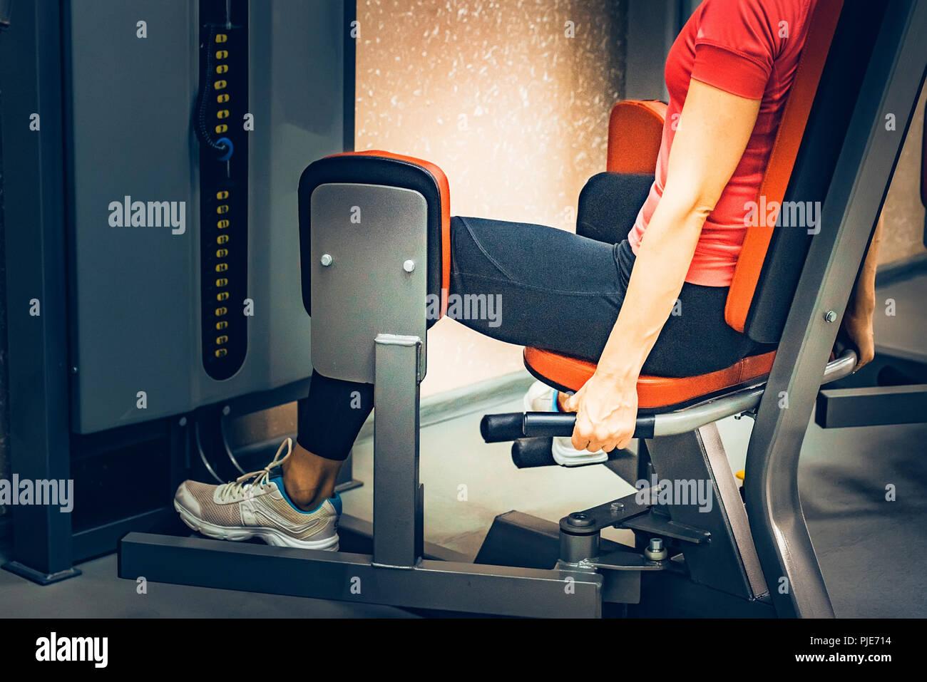 Mujer joven hace ejercicios para las piernas en el gimnasio Imagen De Stock