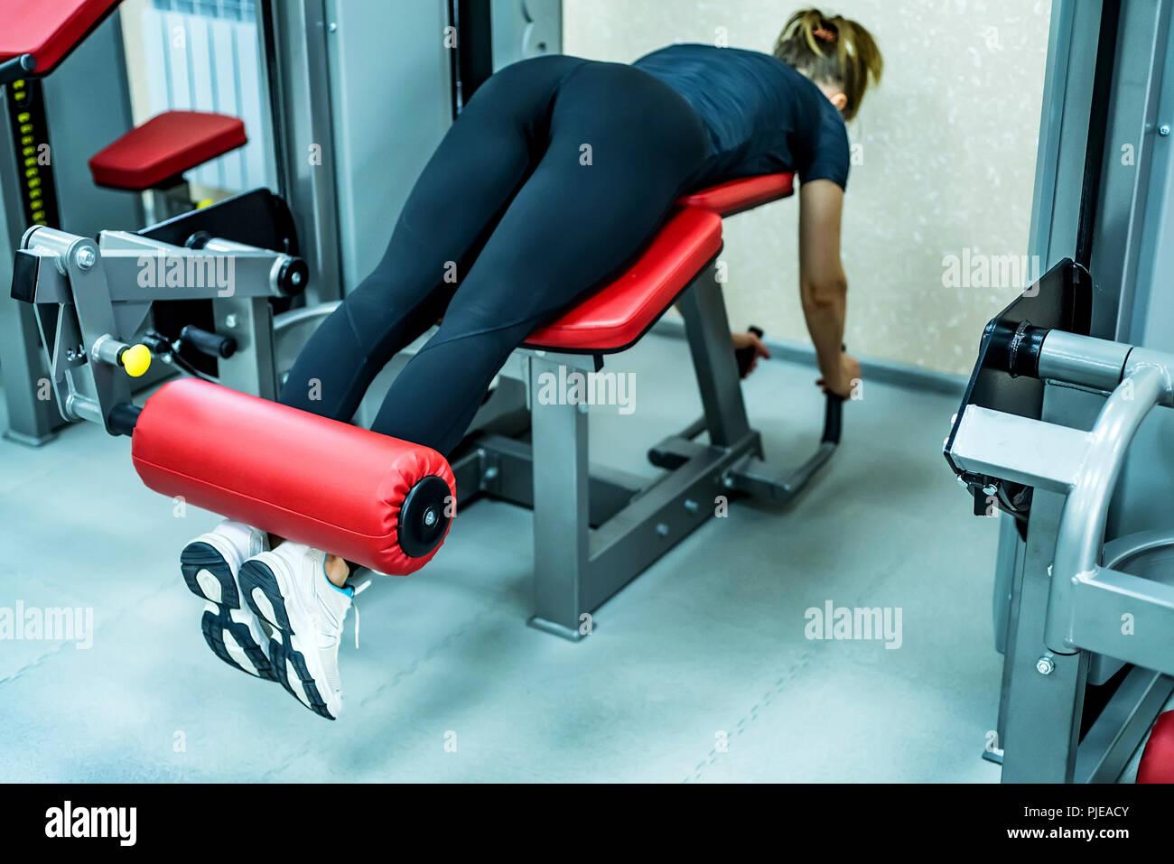 Mujer joven hace ejercicios para las piernas en el gimnasio tumbado Imagen De Stock