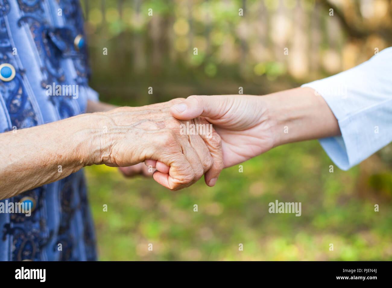 Cerrar imagen de joven mujer sosteniendo su abuela senior arrugadas manos Foto de stock