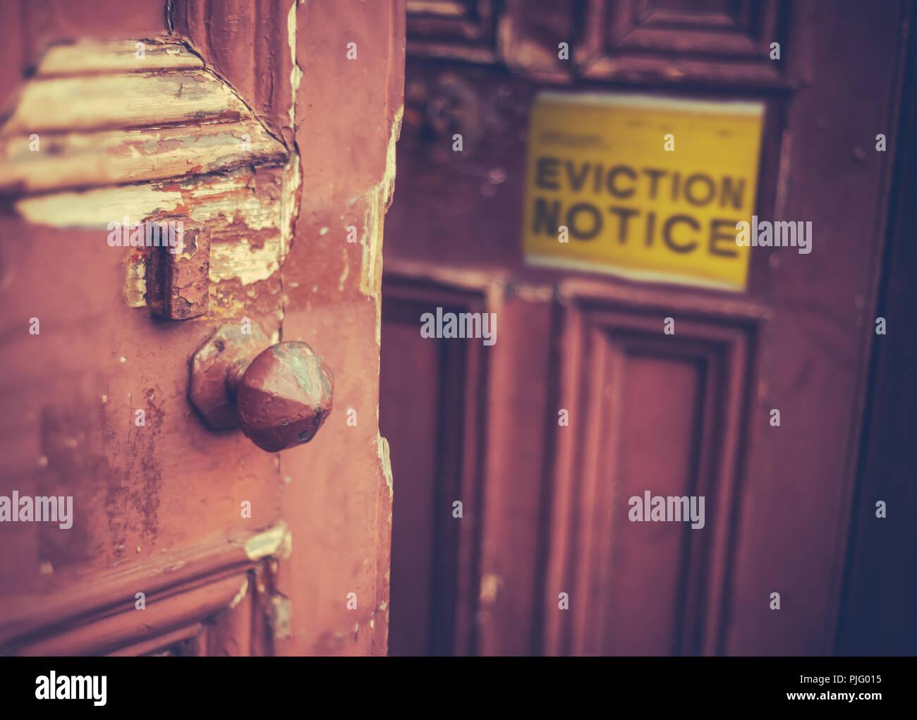 Sucio Antigua puerta con un aviso de desalojo amarillo Imagen De Stock