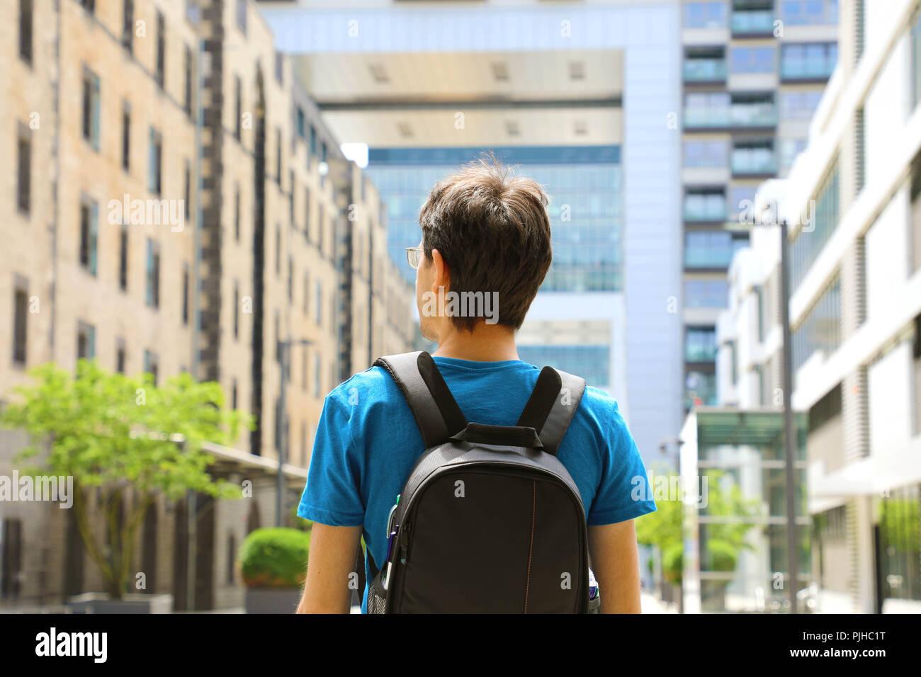 Vista posterior de un hombre joven con mochila acaba de llegar en una gran ciudad y buscan edificios modernos con perspectivas y oportunidades, de la ciudad de Colonia. Imagen De Stock