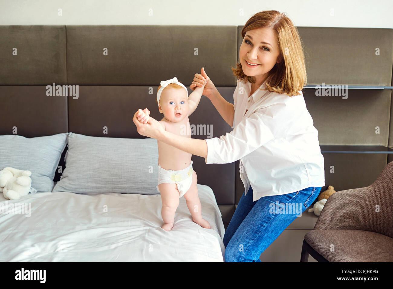 Una feliz abuela juega con un bebé nieto en la cama. Imagen De Stock