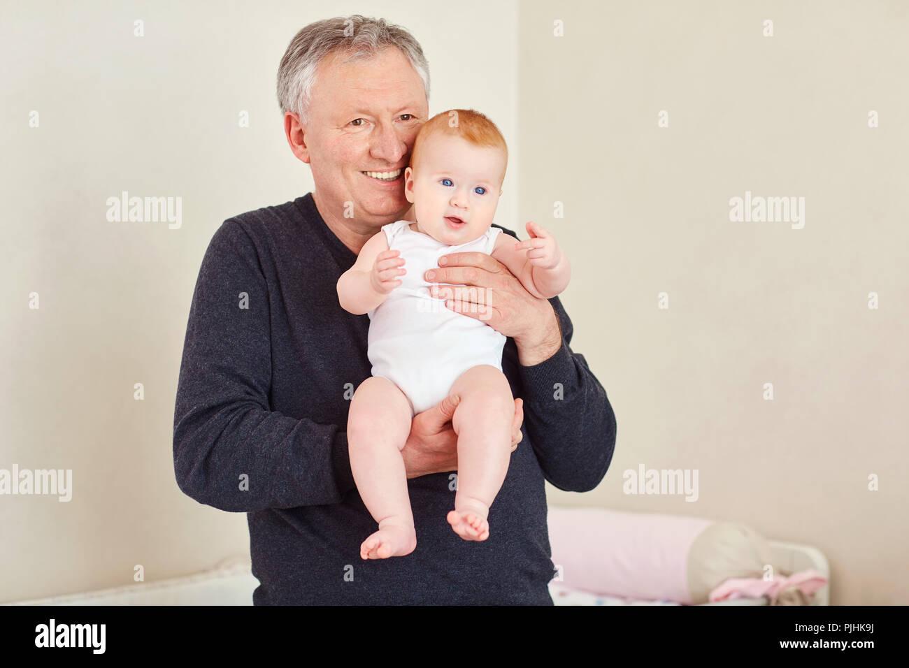 Abuelo sosteniendo un bebé en sus manos. Imagen De Stock