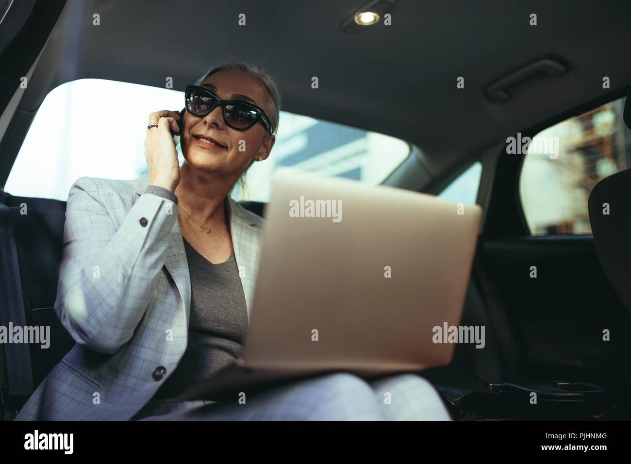 Emprendedor femenino viaja a Office en un lujoso coche sentado en backseat con portátil y mirando fuera de la ventana mientras habla por teléfono . Ma Imagen De Stock