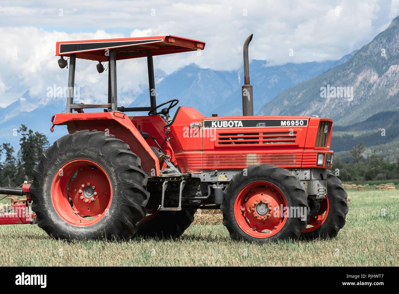 Brisco,BC / Canadá - 11 de julio de 2018:Granja tractor en un campo de heno en las Rocosas Canadienses. Foto de stock