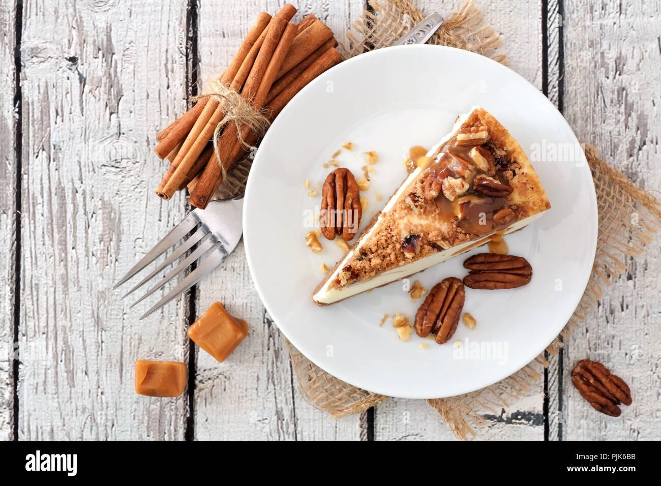 Rodaja de Pecan Caramel cheesecake, vista superior sobre un fondo de color blanco, de madera rústica Imagen De Stock