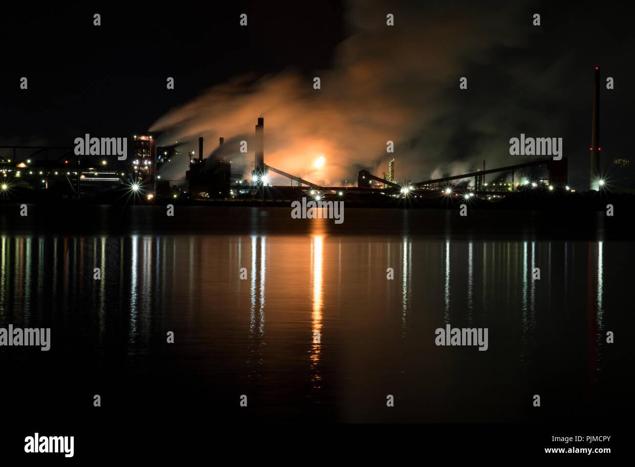 Las fábricas contaminantes y aumentar el calentamiento global. Ocupado en la acería industrial bombeo nocturno de humo en el medio ambiente. Foto de stock