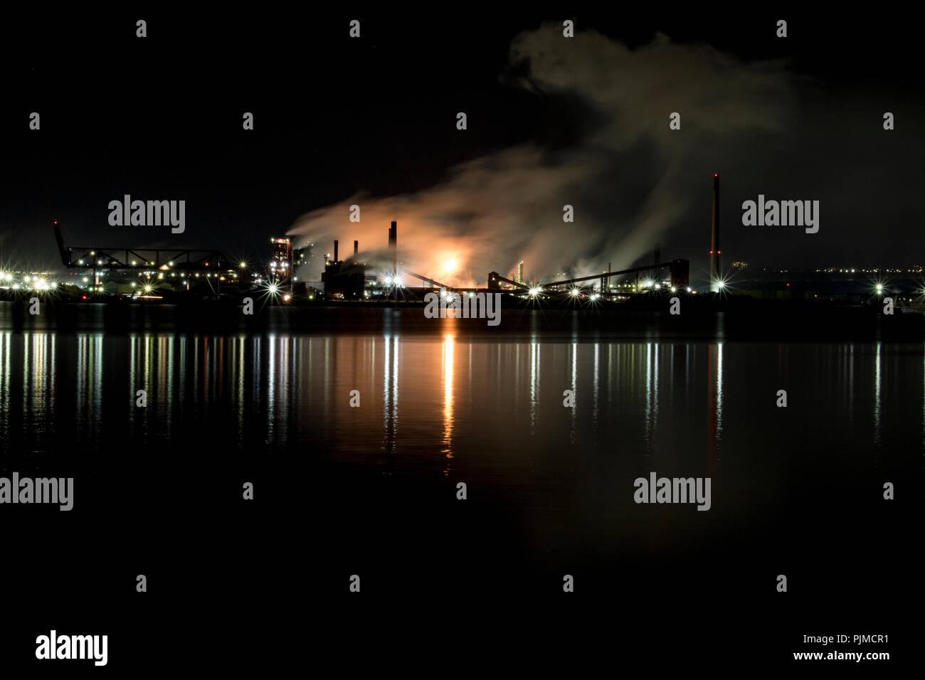 Las fábricas contaminantes y aumentar el calentamiento global. Ocupado en la acería industrial bombeo nocturno de humo en el medio ambiente. Time lapse vid Foto de stock