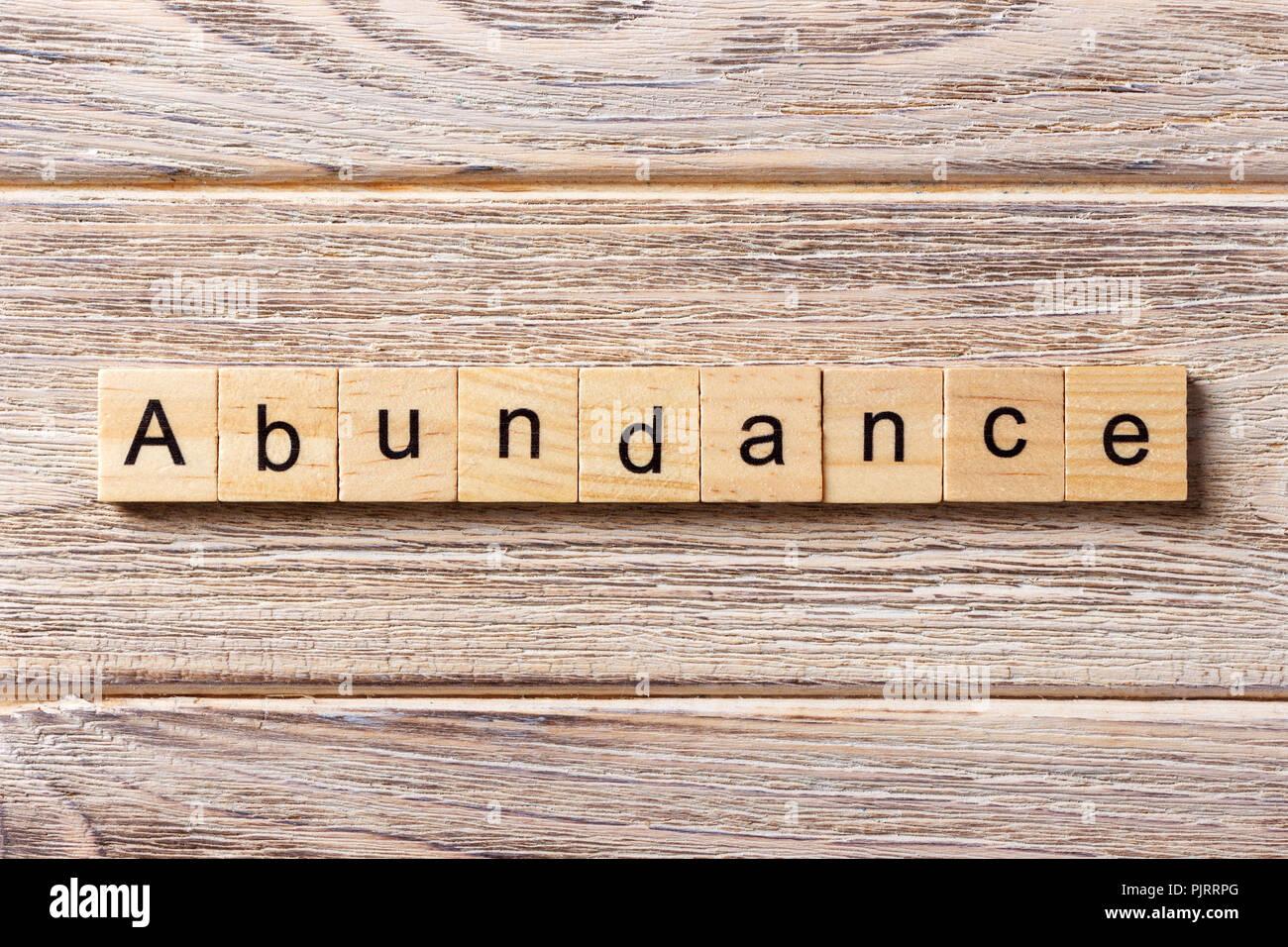 Abundancia palabra escrita sobre un bloque de madera. Abundancia de texto en tabla, concepto. Imagen De Stock