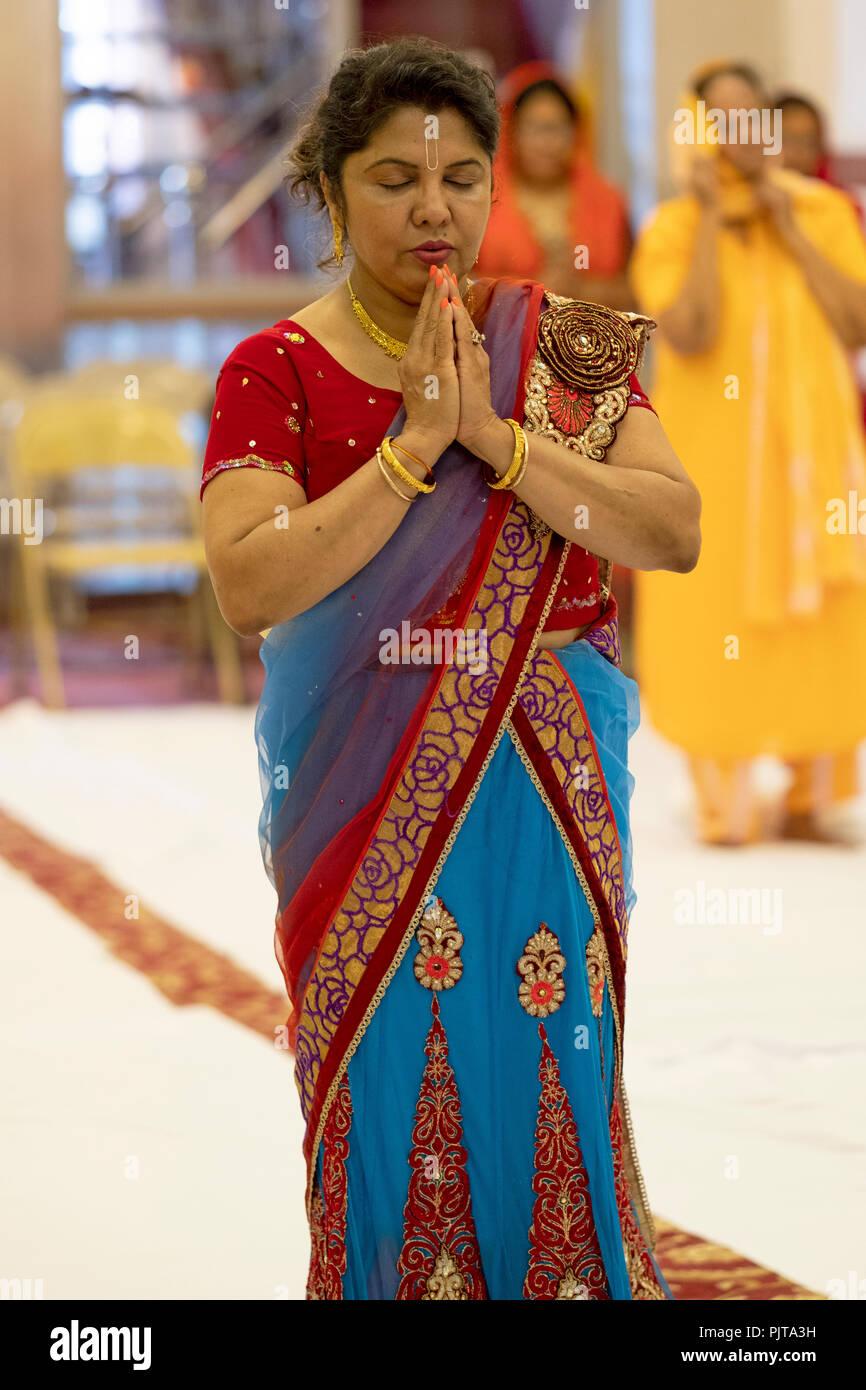 Longitud de tres cuartas partes de un retrato de una mujer hindú rezando y meditando en un templo en el sur de Richmond Hill, en el barrio de Queens, Ciudad de Nueva York. Imagen De Stock