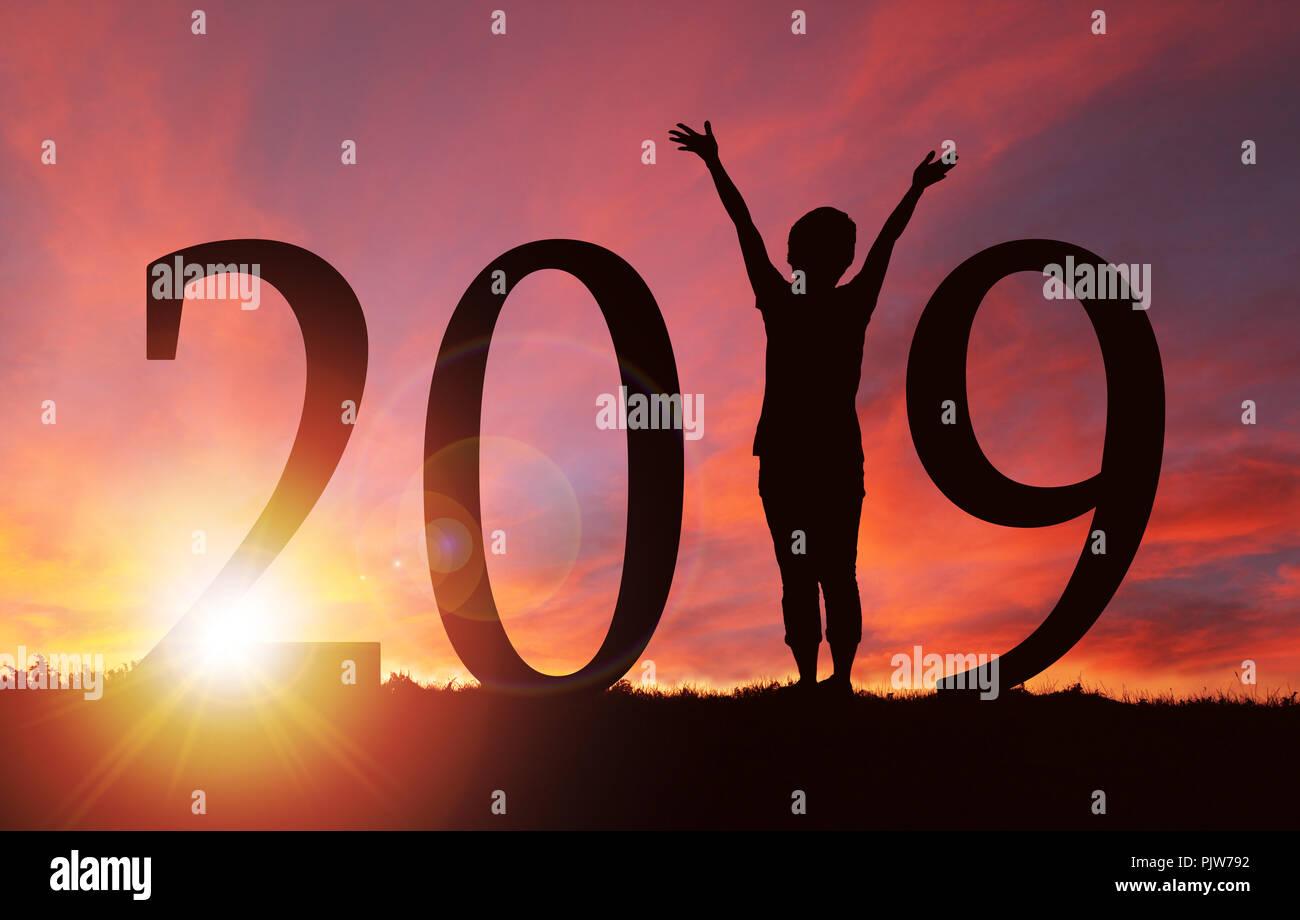 2019 Año Nuevo silueta de una niña con las manos elevadas durante un amanecer o atardecer dorado con espacio de copia. Concepto de alegría, alabanza, adoración, conexión con Foto de stock