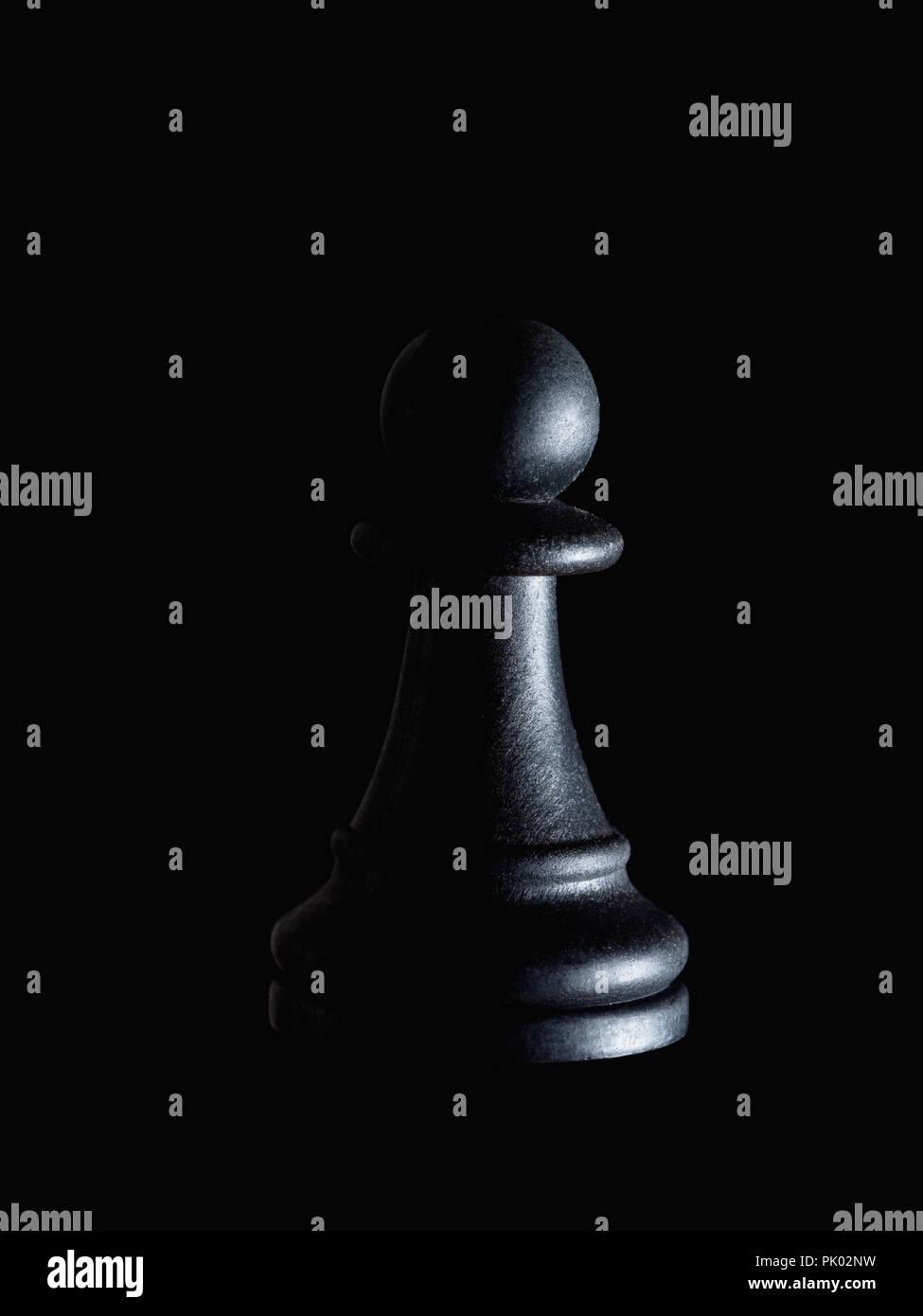 Sola pieza de ajedrez Peón negro sobre negro, una iluminación espectacular. La manipulación, la impotencia, el concepto de víctima ocultos. Imagen De Stock
