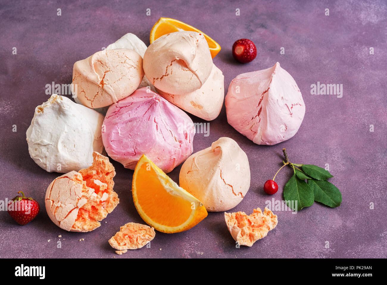 Merengue multicolores con fresas, cerezas y naranja en un hermoso telón de fondo. Un montón de merengue, el enfoque selectivo Imagen De Stock