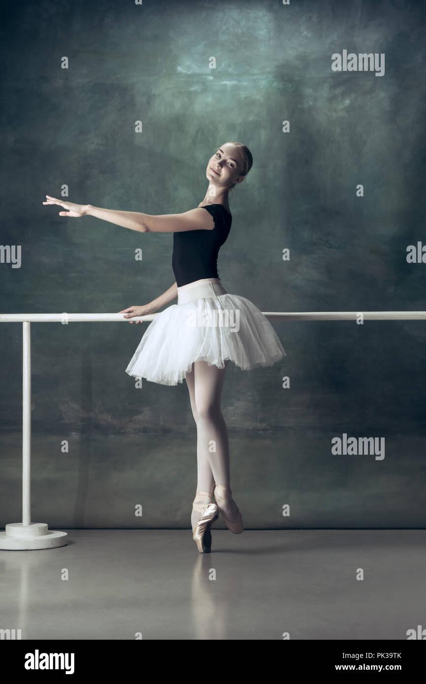 2797bda03 El bailarín de ballet clásico en blanco tutu posando en barra de ...