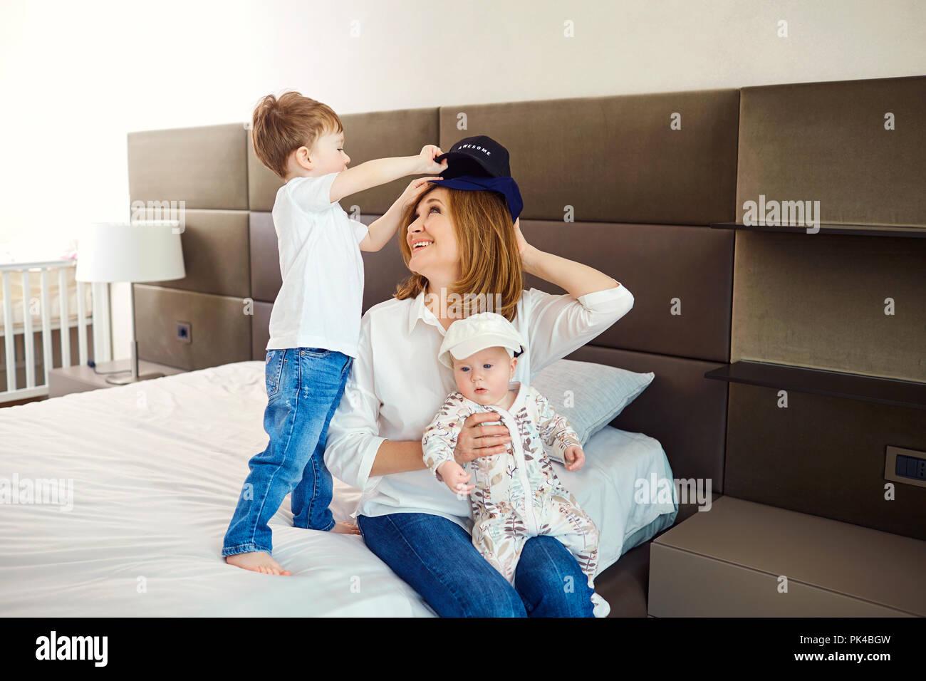 Abuela con sus nietos en la cama en la habitación. Imagen De Stock