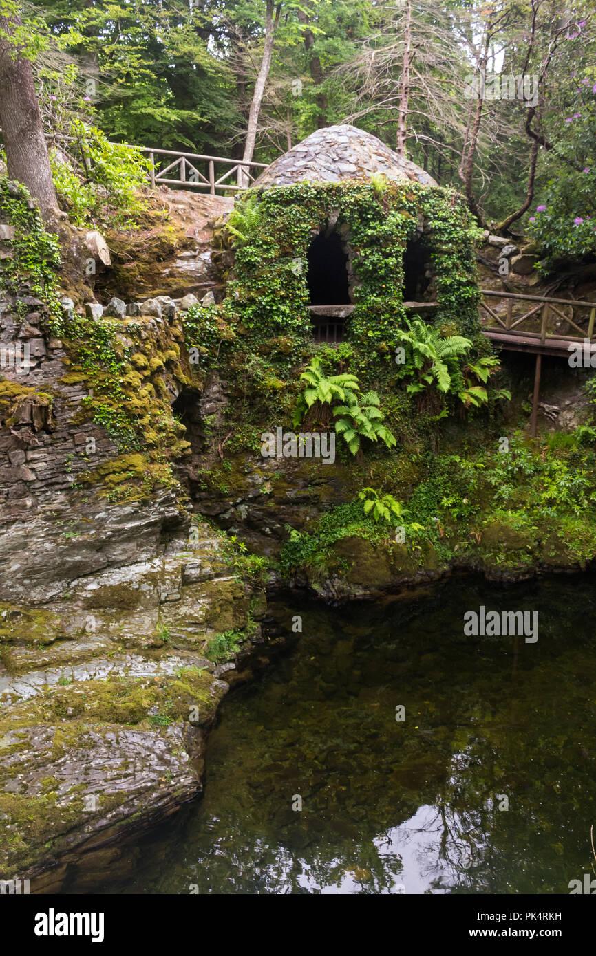 La ermita en Tollymore Park, es un bonito refugio de piedra cubierto de hiedra en un paseo junto al río Shima, Newcastle, Condado de Down, N. Foto de stock