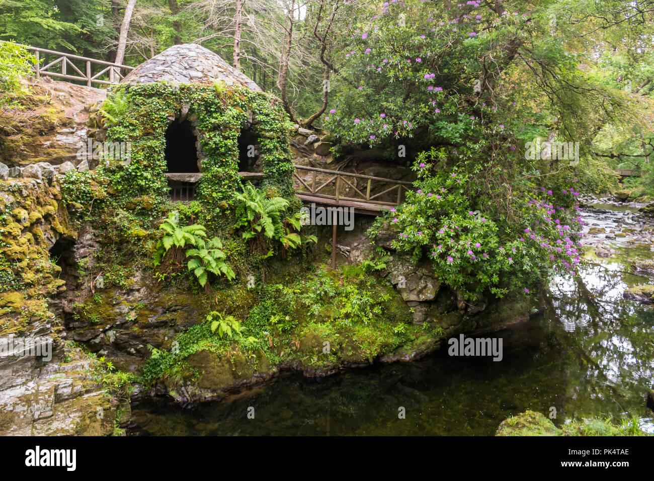 La ermita y el río, la Ermita En Tollymore Park, es un bonito refugio de piedra cubierto de hiedra en un paseo junto al río Shimna Foto de stock