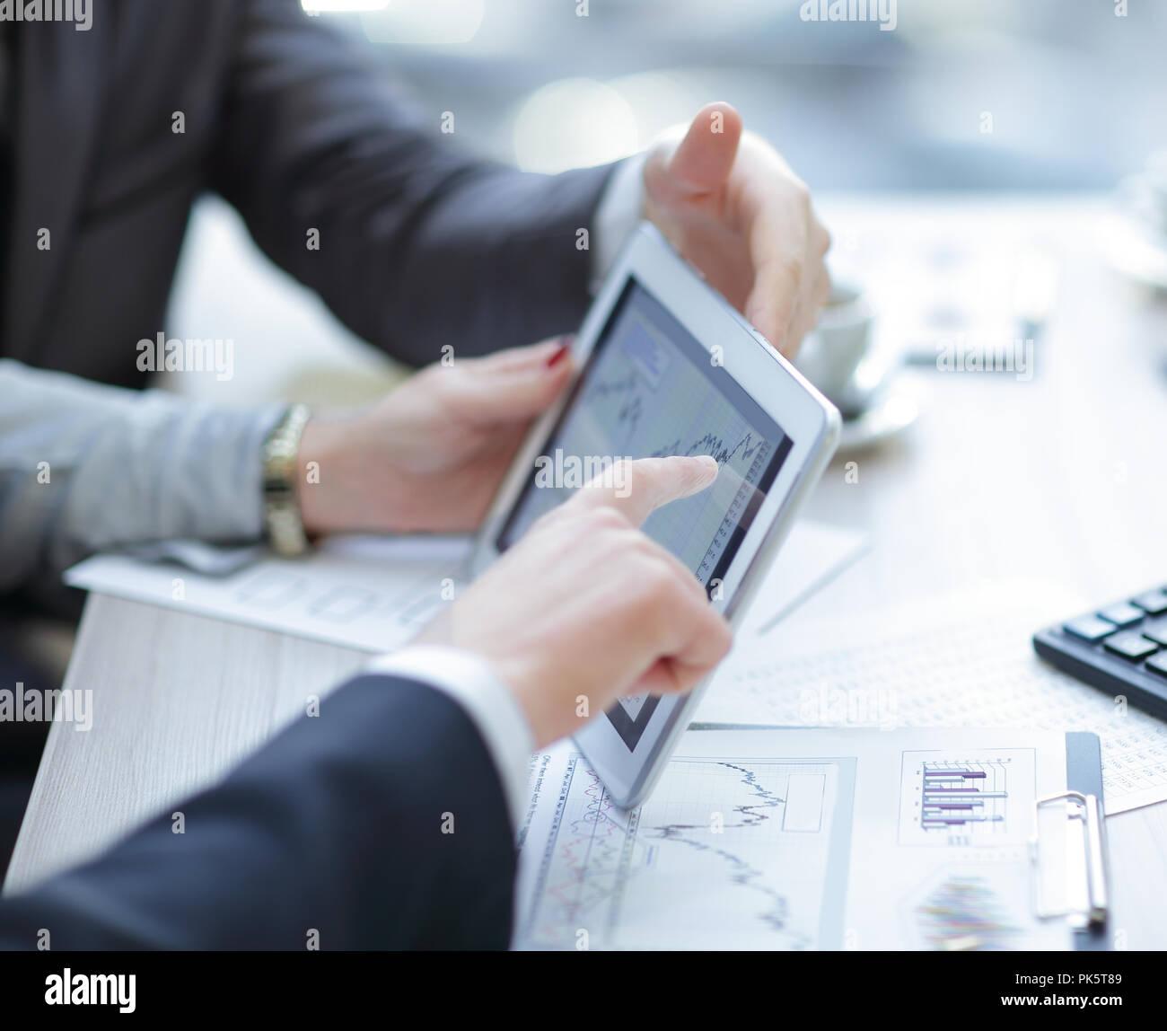 Close up.Equipo empresarial discutiendo gráficos financieros mediante tableta digital. Foto de stock