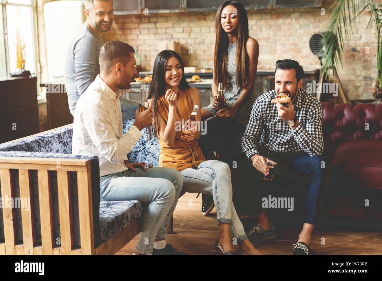 Pasar grandes momentos con los mejores amigos. Grupo de alegres jóvenes disfrutando de una comida y bebidas, mientras que el gasto en buen tiempo cofortable sillas en la cocina juntos. Imagen De Stock