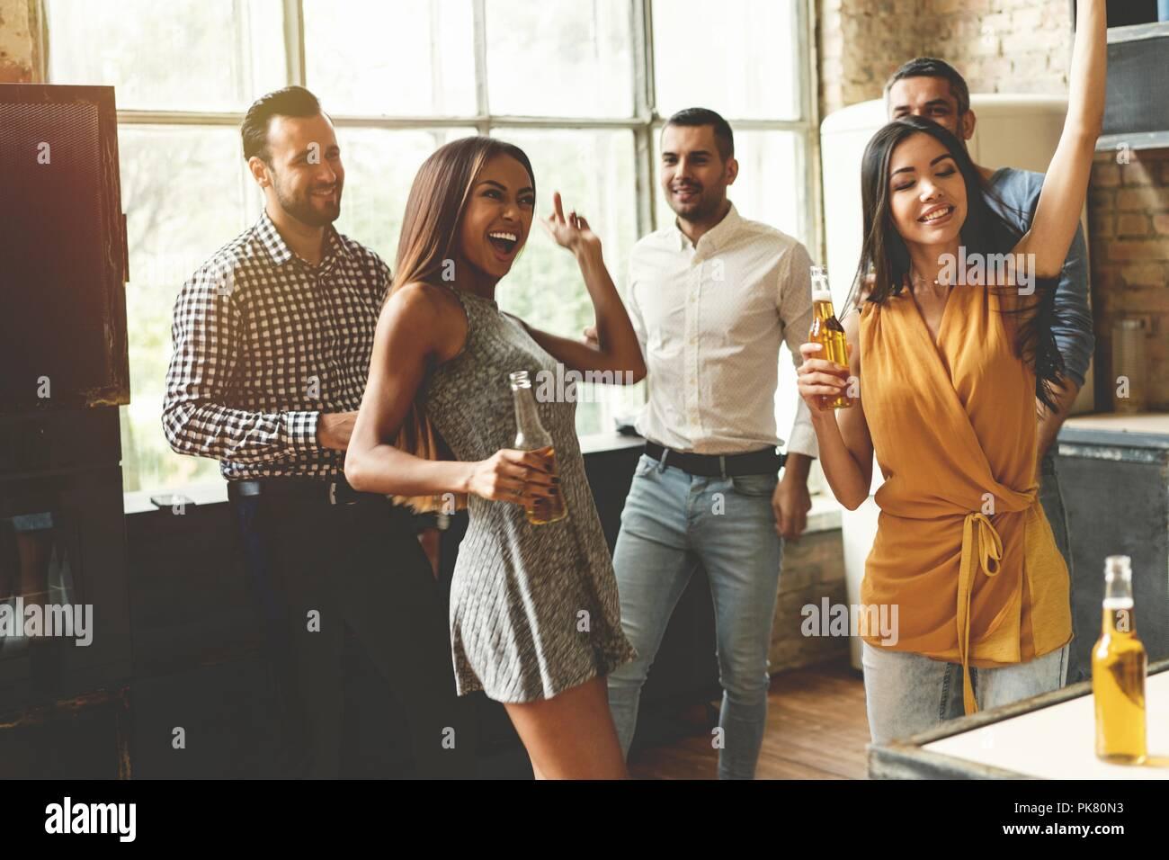 Disfruta de la mejor fiesta con los amigos. Alegres jóvenes bailando y bebiendo mientras disfruta del partido en casa en la cocina. Imagen De Stock