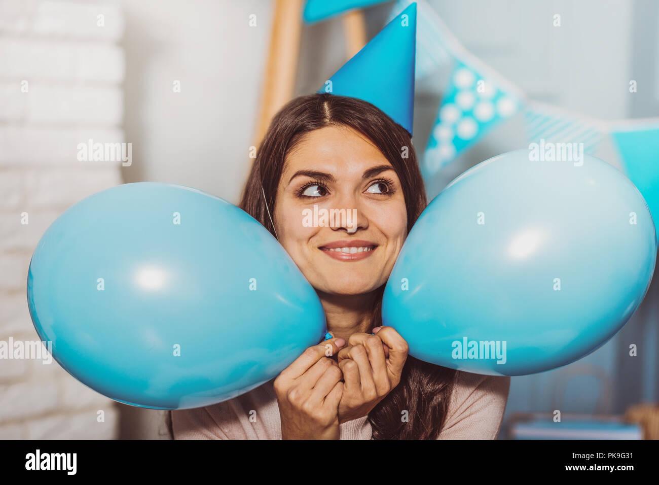 Bastante jolly mujer soñando con fiesta de cumpleaños Imagen De Stock