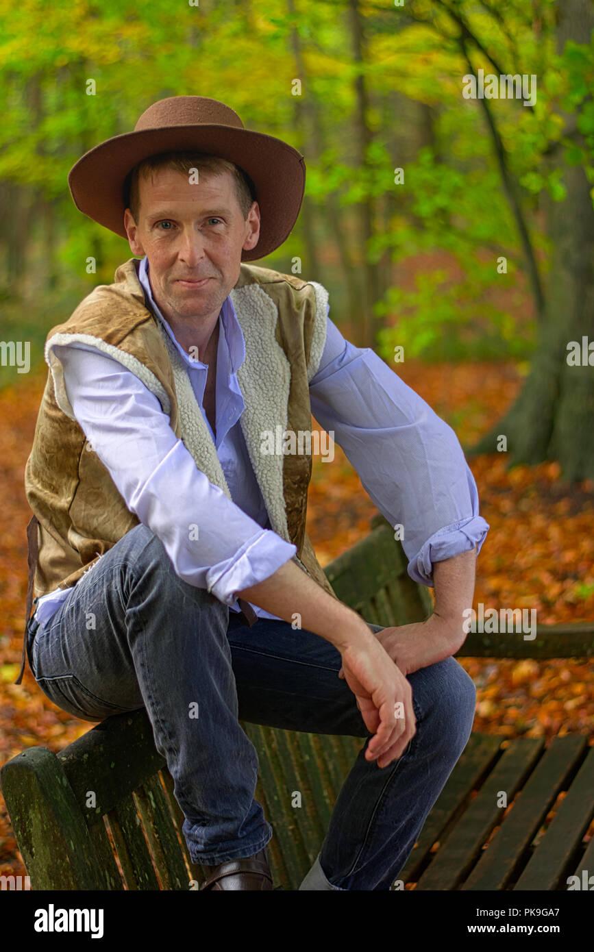 Un hombre vestido como un vaquero sitios en un banco de madera Foto ... 32b6d79c3677