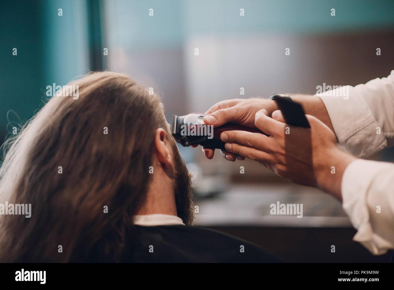 Peluquería hace hombre de peinado. Modelo barbudo hombre y Barber mano. Imagen De Stock
