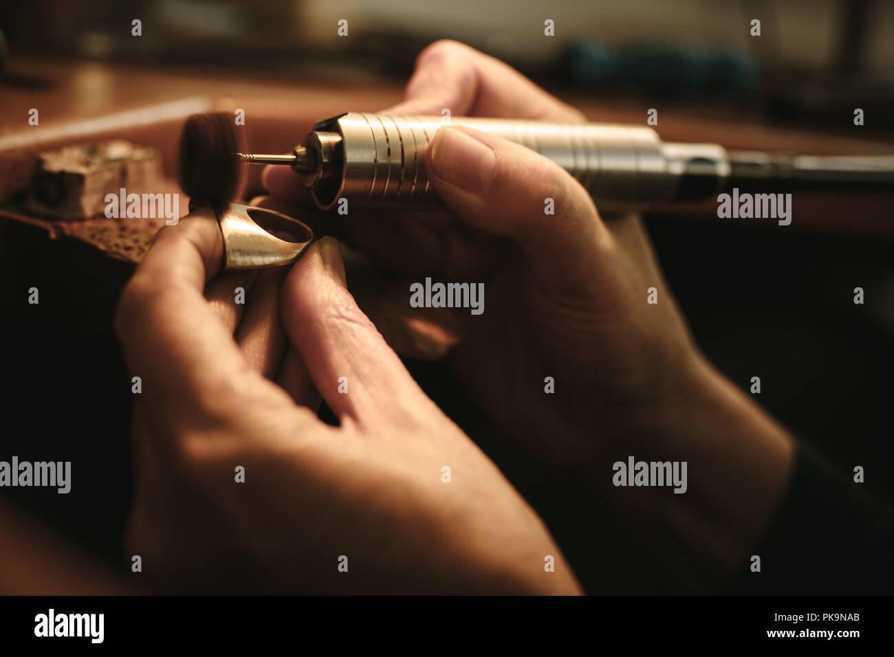 a58de6139c73 Manos de mujer jeweler pulir un anillo con superficie máquina de moler.  Goldsmith haciendo una