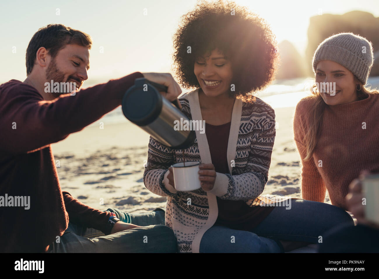 El hombre vierte café en taza de mujer en la playa. Grupo de jóvenes amigos con café en la playa. Imagen De Stock