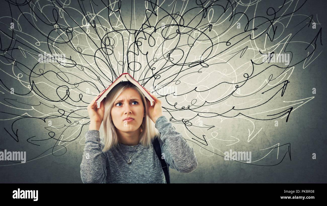 Confundido joven estudiante sosteniendo un libro abierto sobre la cabeza. Emoción triste, infeliz sentimiento, tarea difícil de resolver. Cientos de flechas y curvas goi Imagen De Stock