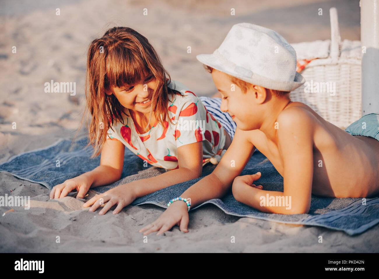 Felices los Niños positivos jugando mientras está acostada sobre una toalla en la playa. Vacaciones de verano y el concepto de estilo de vida saludable Imagen De Stock