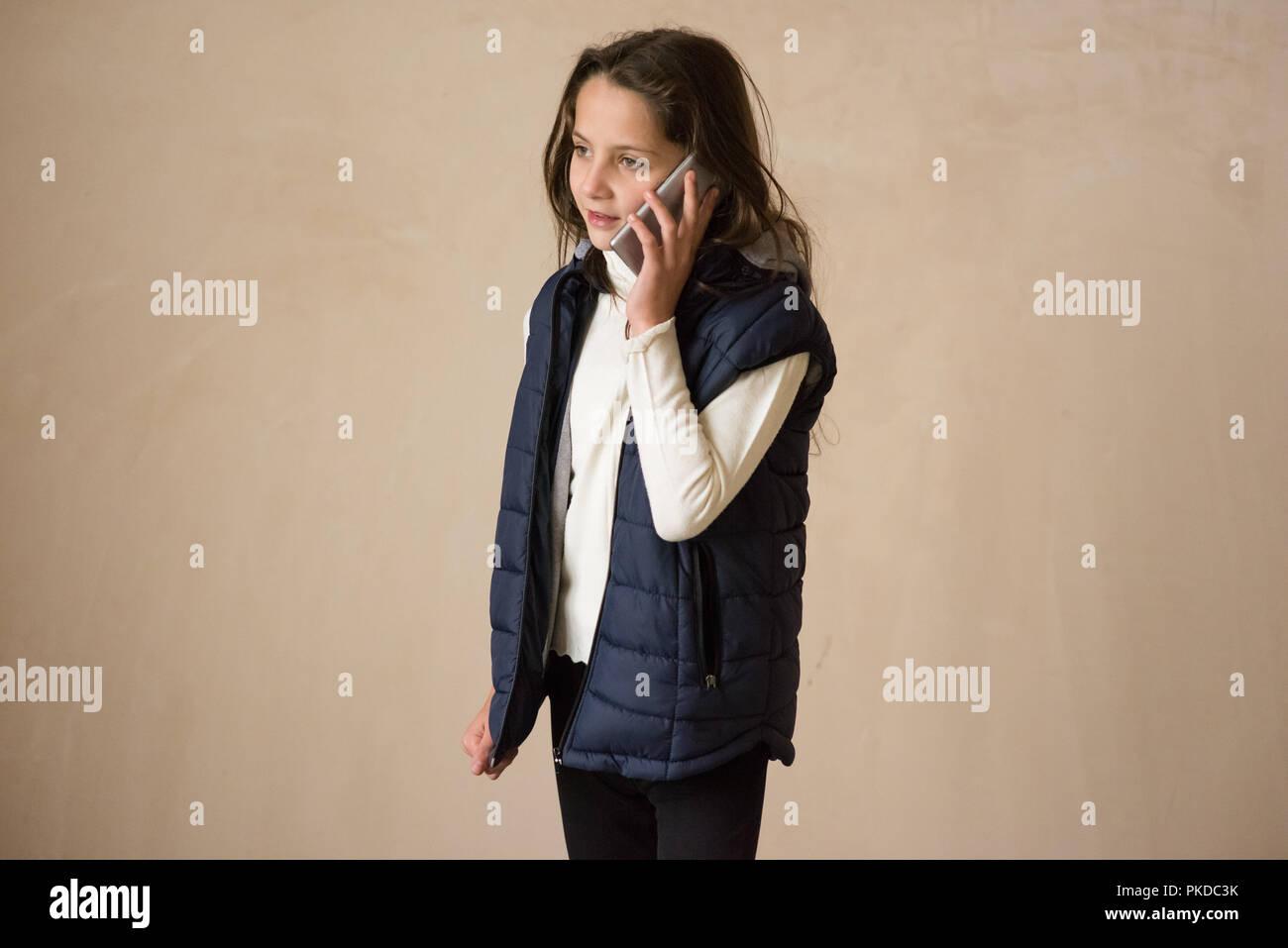 Hermosa niña chaqueta sin mangas hablando por teléfono celular Imagen De Stock