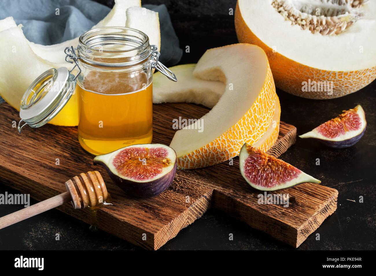 Melón fresco, miel e higos. Snack de frutas el enfoque selectivo. Imagen De Stock