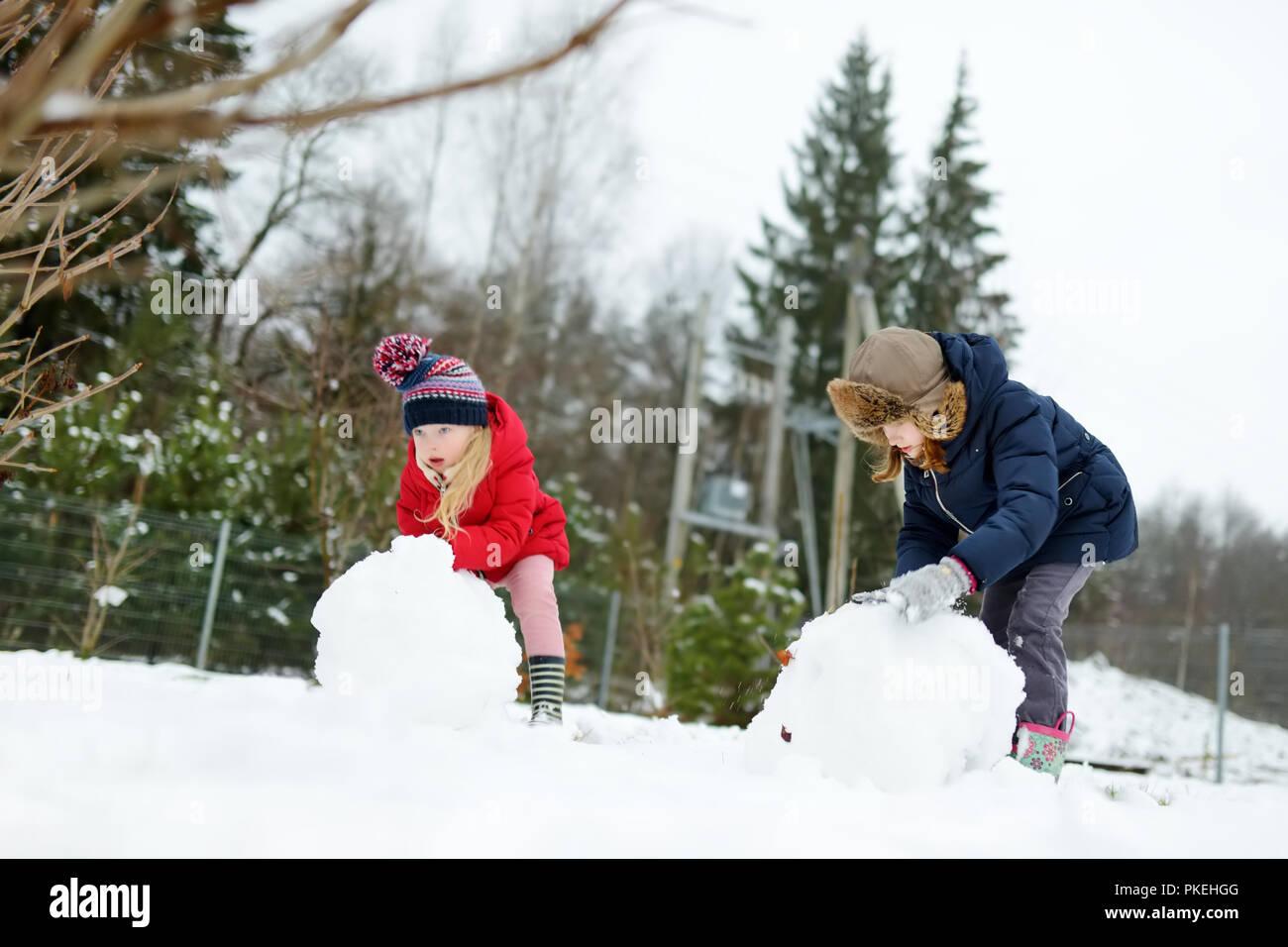 Adorable Pequeño Niñas Haciendo Un Muñeco De Nieve En El Patio Cute Niños Jugando En La Nieve Las Actividades De Invierno Para Los Niños Fotografía De Stock Alamy