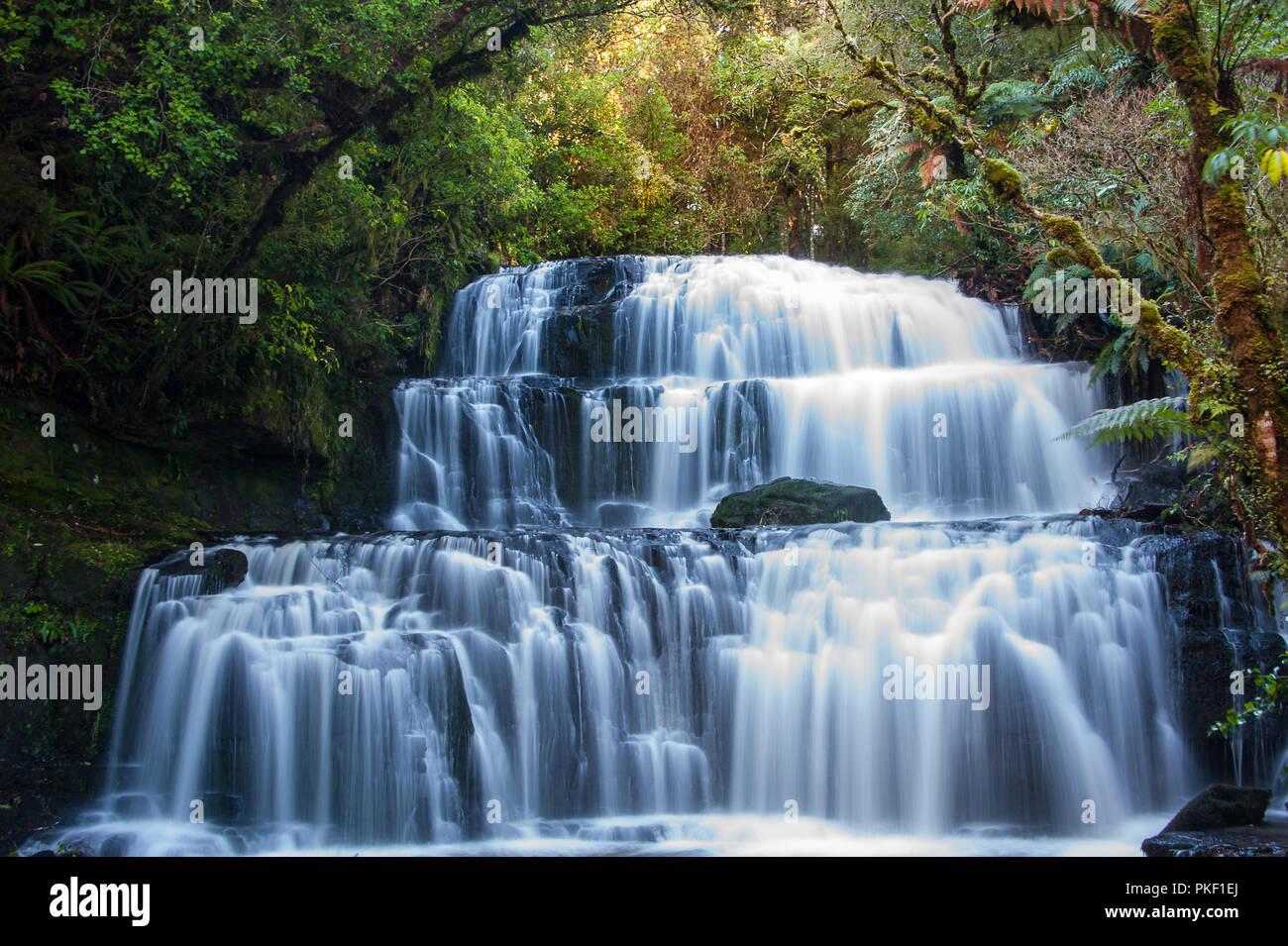 Purakaunui Falls, Los Catlins, la Región de Otago, Nueva Zelanda. Majestic, multi-tiered cae rodeado por la selva antecedentes Foto de stock