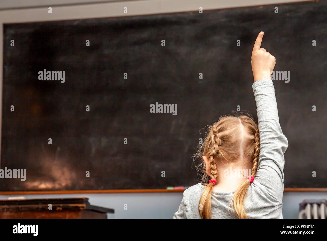 Concepto de educación primaria pública con la joven levantando su mano en el aula. Imagen De Stock