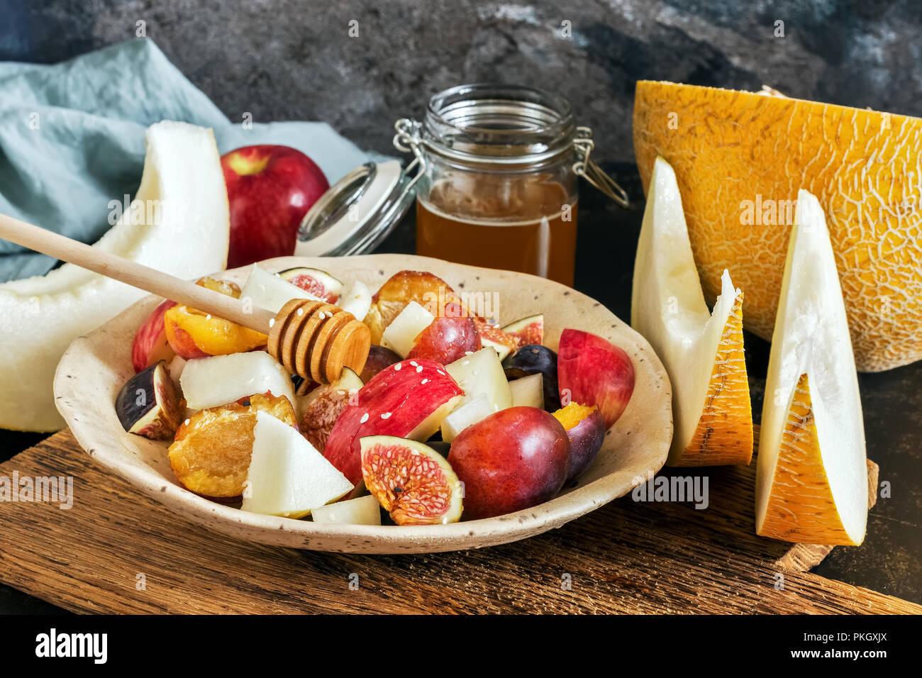 Ensalada de frutas frescas de melón, higos, manzanas, ciruelas y miel. Enfoque selectivo Imagen De Stock
