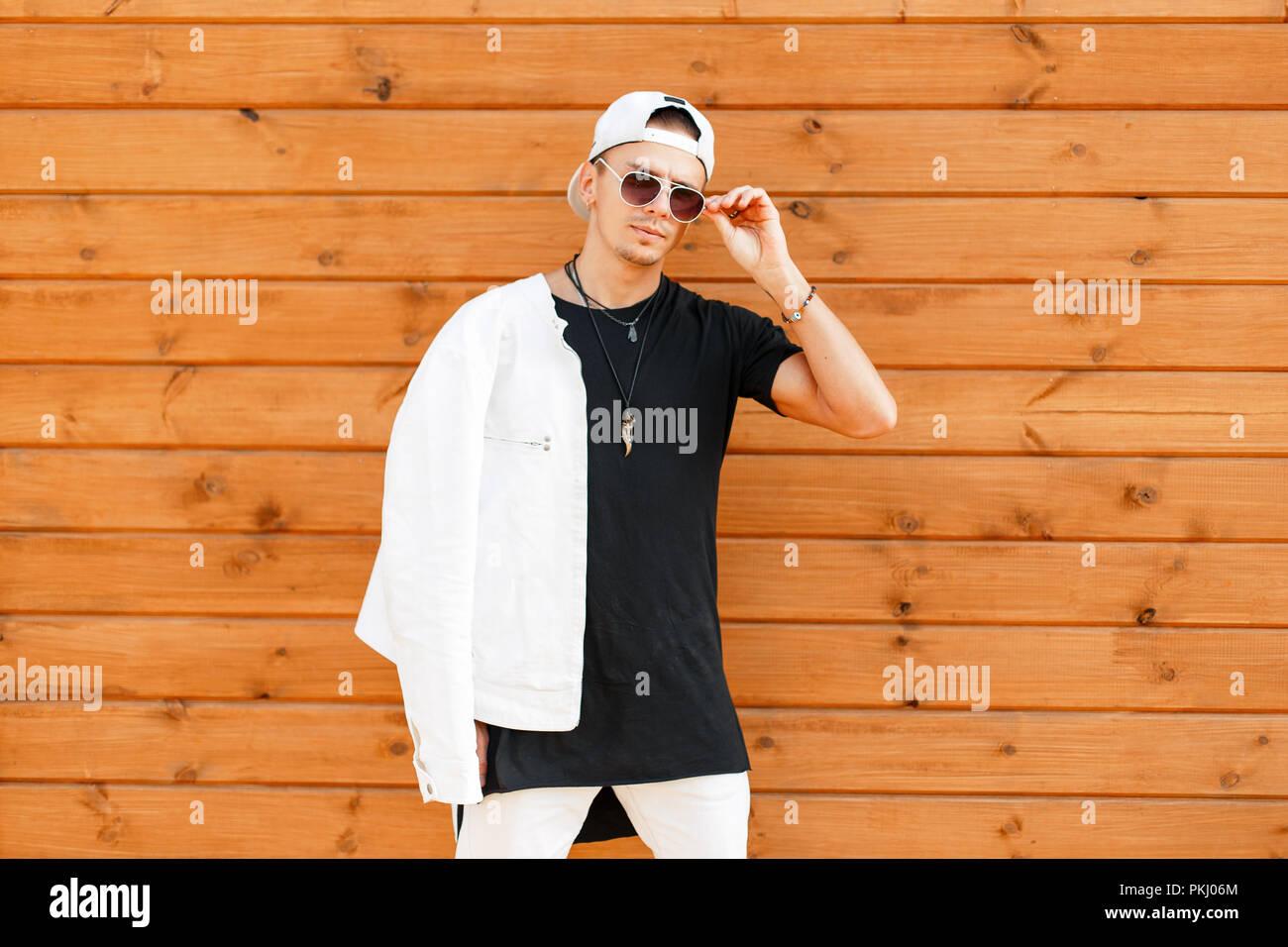 9899fbc91208 Elegante Joven Hombre con gafas de sol en una camisa blanca y una ...