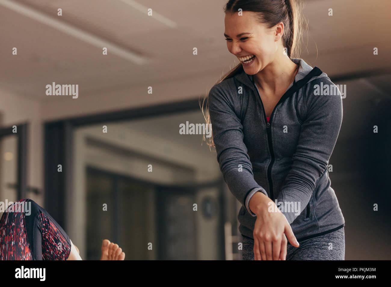 Entrenador femenino mujer rectores durante el entrenamiento pilates en un gimnasio. Instructor de pilates femenino riendo mientras que la capacitación a la mujer en un gimnasio. Imagen De Stock