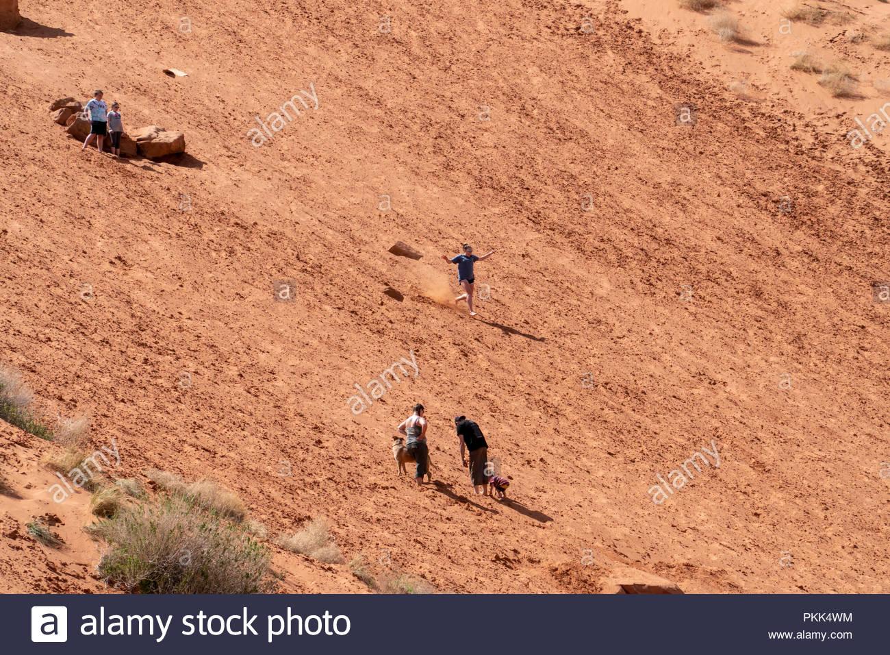 Una joven mujer corre de bruces una gran montaña de arena justo en las afueras de Moab, Utah, EE.UU. Imagen De Stock