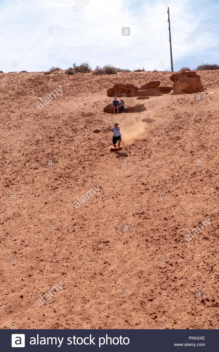 Un joven corre de bruces una gran montaña de arena justo en las afueras de Moab, Utah, EE.UU. Imagen De Stock