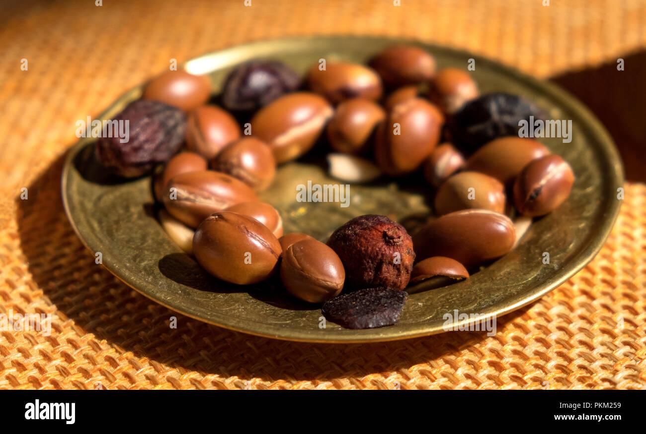 Tuercas de argán semillas en una placa - Argán es útil como antioxidante para curar las inflamaciones de la piel enrojecimiento de las estrías. Imagen De Stock