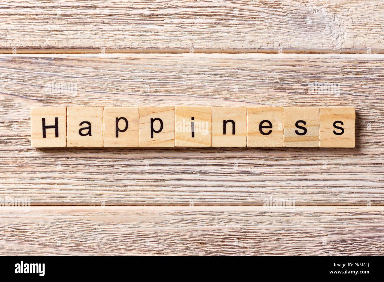 Felicidad palabra escrita sobre un bloque de madera. Felicidad texto en tabla, concepto. Imagen De Stock