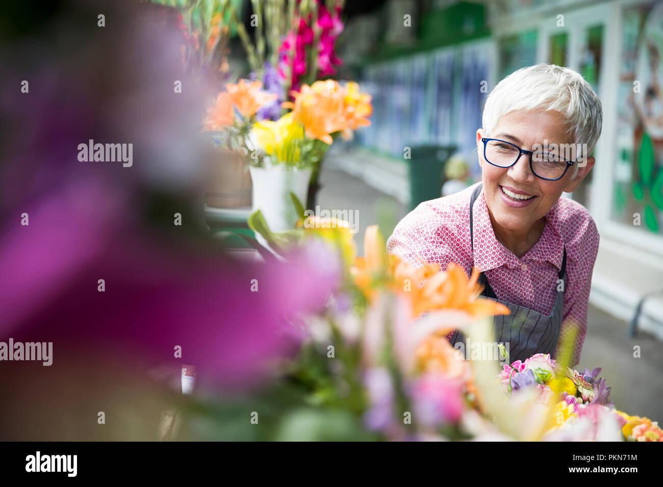 Senior Charrming mujer arregla flores en el mercado local. Imagen De Stock