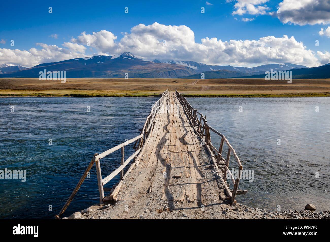 Desvencijado puente de madera sobre un río con lejanos cordillera en el fondo, las montañas de Altai, Mongolia occidental Foto de stock