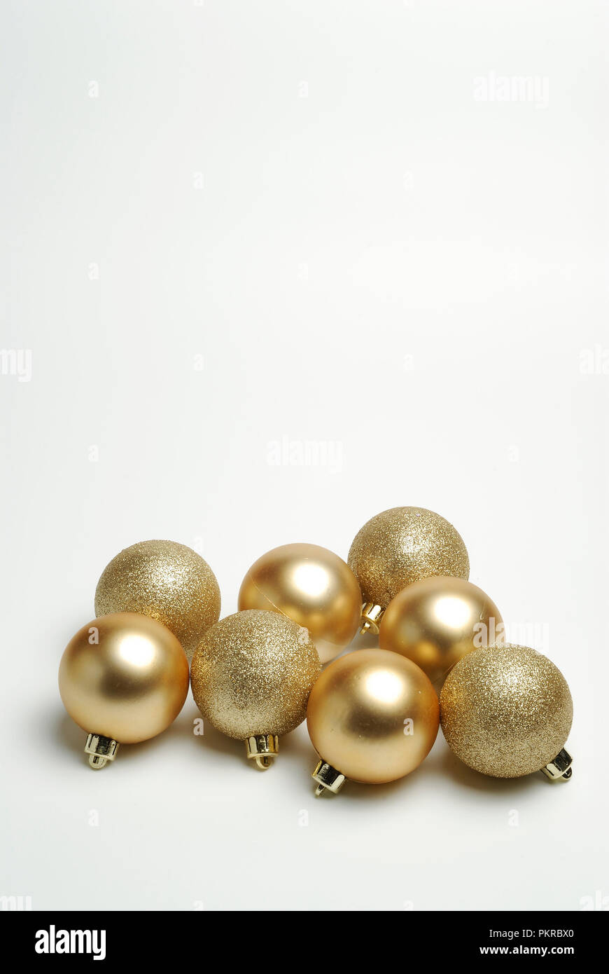 Bolas decorativas doradas sobre fondo blanco. Imagen De Stock